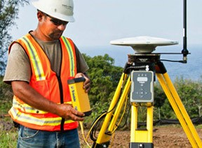 Construction Worker on Site Using Trimble Technology for Site Positioning